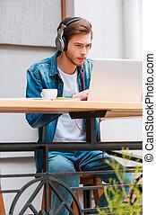 saída, de, mundo, com, meu, música, e, laptop., concentrado, homem jovem, em, fones, trabalhar, laptop, enquanto, sentando, em, bar calçada