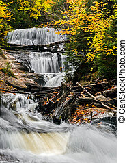 Sable Falls, a waterfall in Upper Peninsula Michigan's Pictured Rocks National Lakeshore, cascades through an autumn landscape of boulders and fallen trees.