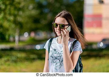sac à dos, elle, espace, tient, text., adolescent, gratuite, main, écolière, derrière, téléphone., pourparlers, girl, sunglasses., smartphone, il