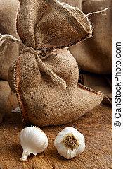 sack with garlic - jute sack with ripe garlic on wooden...