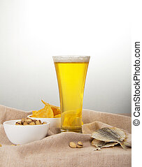 Sackcloth, glass of beer, pistachio, salty fish and fried potatoes on a gray background