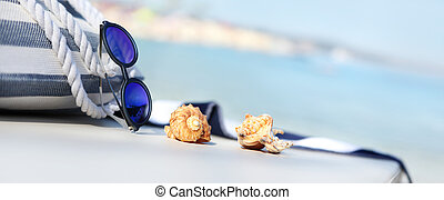 sacola praia, toalha, óculos de sol, conchas