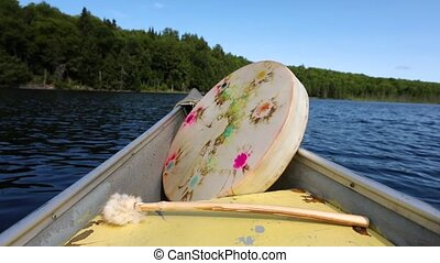 Close up footage of a sacred native drum with dyed stretched membrane and traditional soft wood beater, floating in a canoe on a natural lake, with copy space