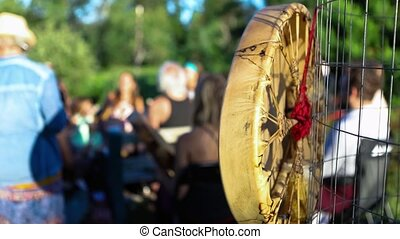 Closeup footage of a handmade indigenous leather drum hanging near a gathering of people as they sit in a singing circle during a mindful shaman ritual.
