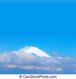 Beautiful sacred Mount Fuji (Fujiyama) in clouds on blue sky background, Japan. Copy space for text