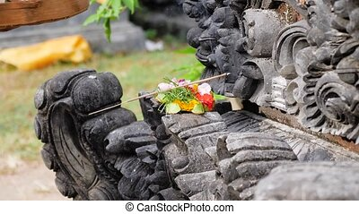 Sacrifices and incense in a Buddhist temple - Woman makes...