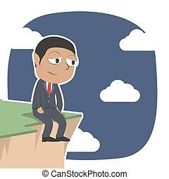 Sad african businessman sitting on cliff edge
