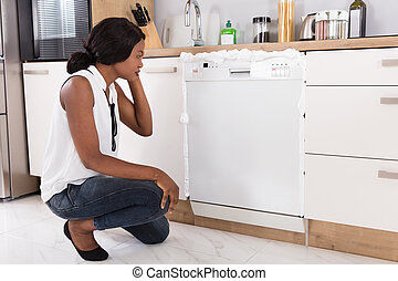Woman Looking At Foam Coming Out From Dishwasher