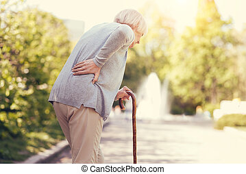 Sad aged woman leaning on the walking stick
