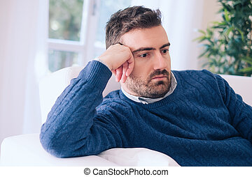 Sad and depressed portrait of man alone at home