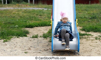 Sad and dissatisfied child girl on the playground expresses...