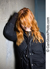Sad and lonely, moody portrait of a beautiful fashoinable young redhead girl.