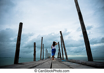 Sad and lonely woman stand alone on a the wooden bridge over the sea