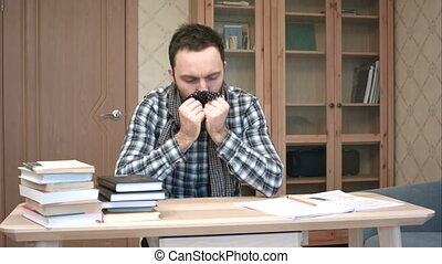 Sad and sick student getting down with flu sitting at the desk with books