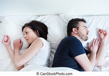 Sad and thoughtful couple after arguing lying in bed