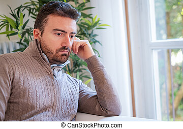 Sad and thoughtful portrait of man alone at home