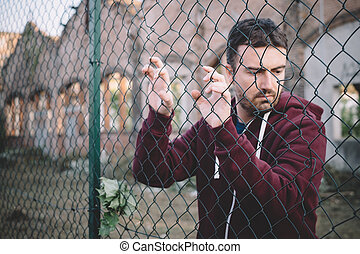 Sad and troubled boy against metal fence