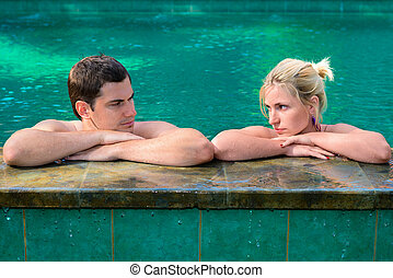 Sad and unhappy couple in swimming pool - Sad couple looking...