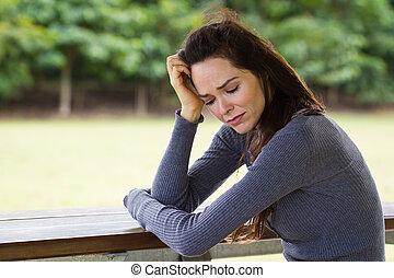 Sad and upset woman sitting outdoors