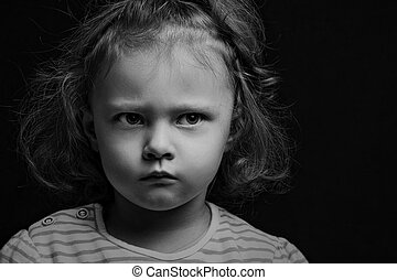 Sad annoyed small kid girl looking up on black background with empty copy space. Closeup studio portrait. Black and white.