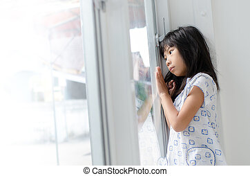 Sad Asian girl at the window