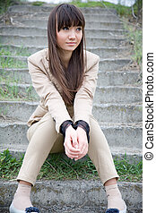 Sad Asian girl sitting on the stairs