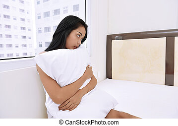 Sad asian woman sitting on bed and hugging a pillow