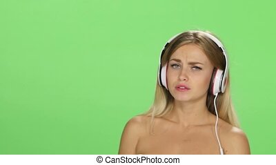 Sad beautiful blonde girl dancing with headphones isolated on a green screen