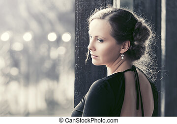 Sad beautiful fashion woman in black dress in a city street