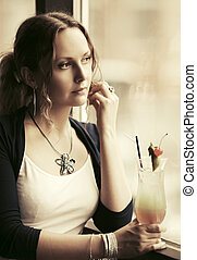 Sad beautiful woman with cocktail looking out window