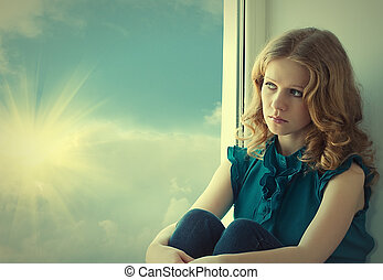 sad, beautiful young woman pining at the window at the sky and sunset