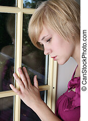 Sad Beauty - Beautiful blond female leaning against a door,...