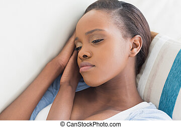 Sad black woman lying in a living room