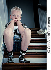 Sad blond boy sits on stairs with elbows on knees