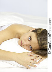 Sad blond woman laying in bed