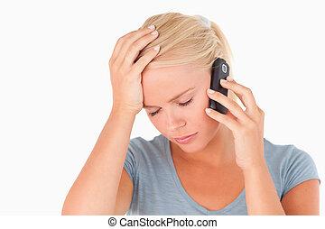 Sad blond woman on a phone