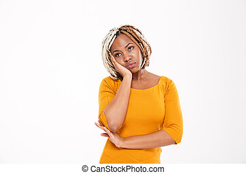 Sad bored african american young woman in yellow dress standing