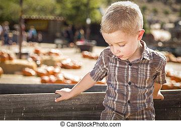 Sad Boy at Pumpkin Patch Farm Standing Against Wood Wagon