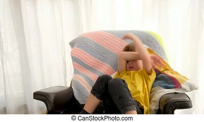 Upset little boy in casual clothes covering eyes while sitting in comfortable armchair at home