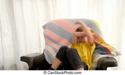 Sad boy crying in armchair