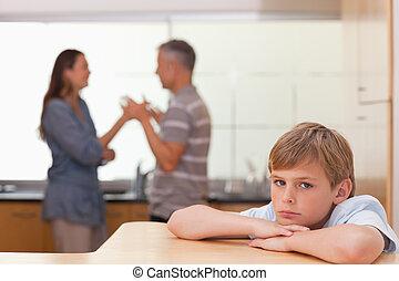 Sad boy hearing his parents having am argument