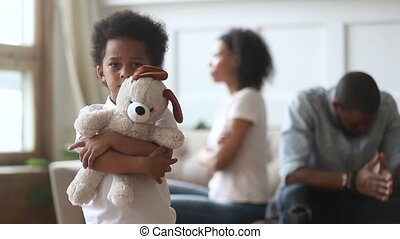 Sad boy holding toy looking at camera, divorce and children...