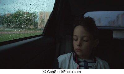 Sad boy inside a car in rainy weather