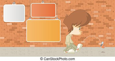 Sad boy kicking a can in front of a orange brick wall with ...