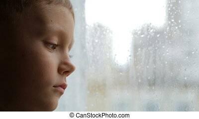 Sad boy looks out the window in rainy weather - The child...