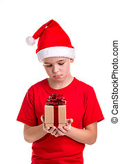 Sad boy, santa hat on his head, with the small gift box in the hands. Concept: christmas or Happy New Year holiday