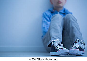 Sad boy sits alone - Sad boy in sneakers with asperger's ...