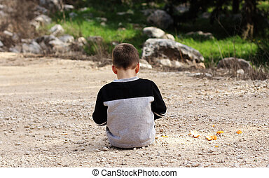 Sad boy sitting alone in nature, autism syndrome
