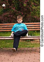 Sad boy sitting on a bench
