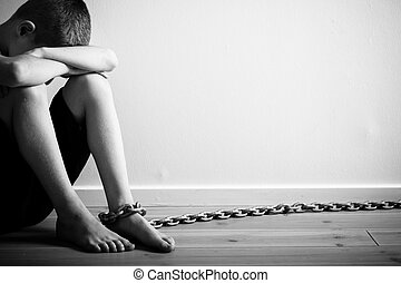 Sad Boy Sitting with Chain on Foot in Monochrome
